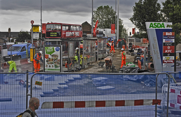 Reconstruction as a branded performance in a branded landscape. Last minute re-paving of bus stops at Leyton Underground station. July 2012
