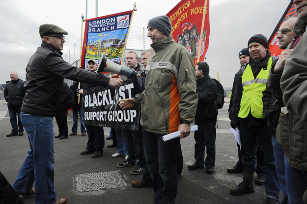 Dave Smith, of the Blacklist Support Group, hands a megaphone to Frank Morris, blacklisted for defending a fellow electrician on the Olympic site against dismissal. Demonstration outside Olympic construction site. May 2009