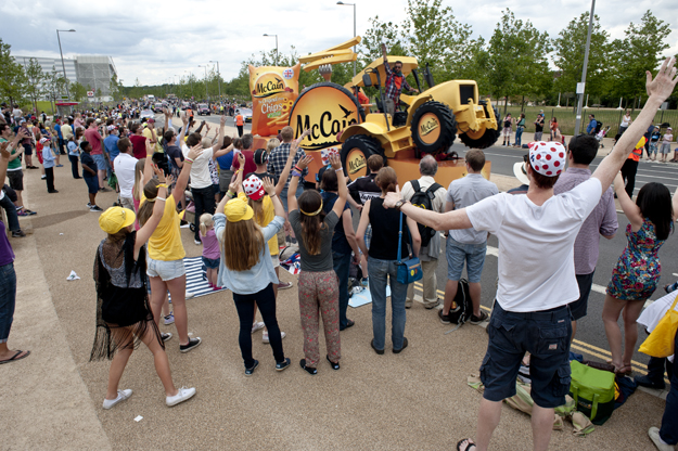 Fans, appealing for freebies, hailing the McCain Oven Chips publicity vehicle. This is part of the promotional cavalcade which precedes the passage of the Tour de France peloton through the Olympic Park. July 2014